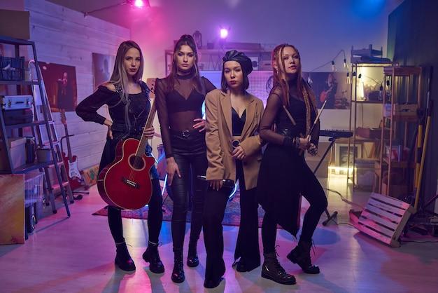 Portrait d'un groupe musical féminin moderne regardant la caméra pendant leur spectacle en boîte de nuit