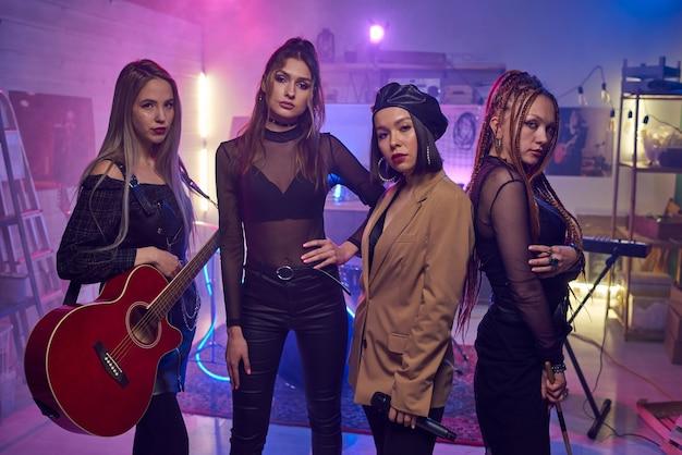 Portrait d'un groupe musical féminin regardant la caméra pendant la performance du concert