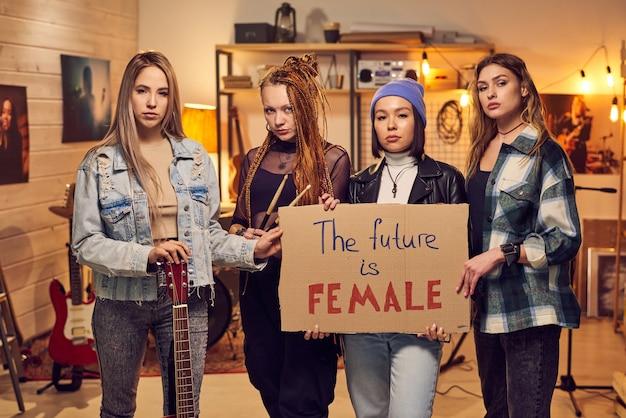 Portrait d'un groupe de musique tenant une pancarte et regardant la caméra en se tenant debout dans un studio de musique