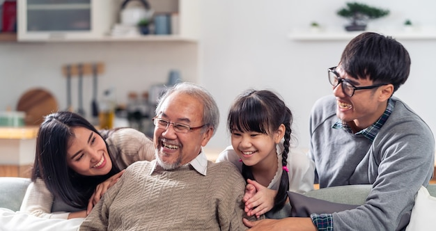 Portrait de groupe panoramique de la famille asiatique multigénérationnelle heureuse s'asseoir sur le canapé-lit dans le salon avec le sourire.