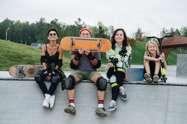 Portrait de groupe de patineurs se prélassant sur le pont du skatepark, s'amusant. porter un équipement de protection. vue frontale. nature en arrière-plan.
