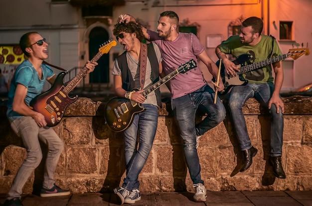 Portrait d'un groupe de rock composé de quatre garçons, représentés avec leurs instruments de musique à la main sur un mur.