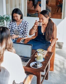 Portrait d'un groupe de trois femmes d'affaires asiatiques qui planifient et discutent de quelques idées assises à table dans un bureau moderne.