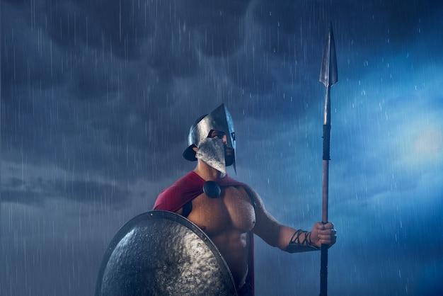 Portrait de guerrier spartiate debout à l'extérieur avec lance et bouclier en soirée. vue de face d'un homme musclé en manteau rouge et casque posant par mauvais temps nuageux et pluvieux. concept antique de sparte.