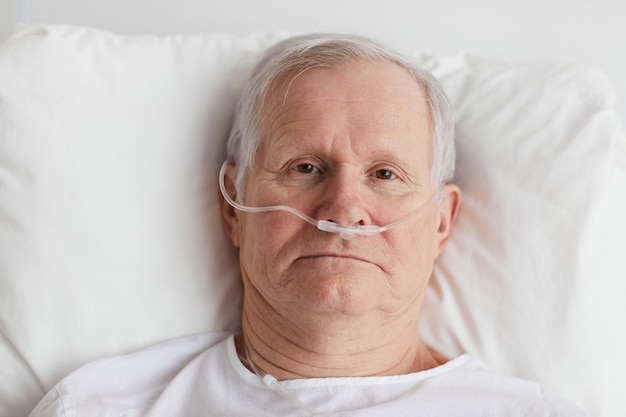 Portrait de haut en bas d'un homme âgé allongé dans un lit d'hôpital avec supplémentation en oxygène et regardant la caméra, espace de copie