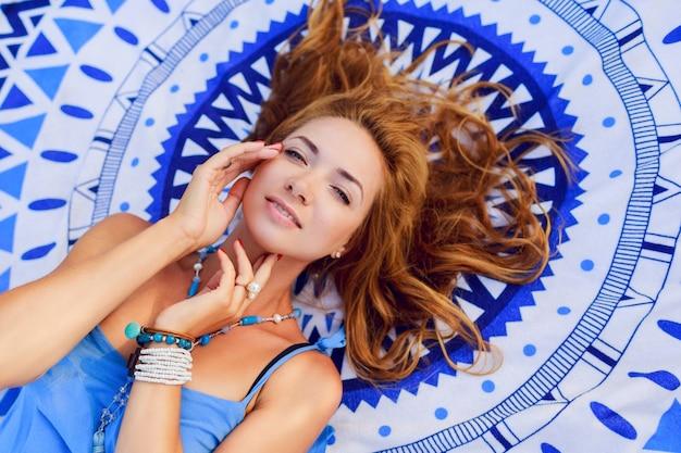 Portrait d'en haut de femme souriante se détendre sur une serviette de plage en journée d'été ensoleillée. bracelets et collier boho élégants.