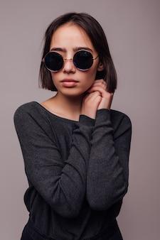 Portrait haute couture de jeune femme élégante à lunettes de soleil isolé