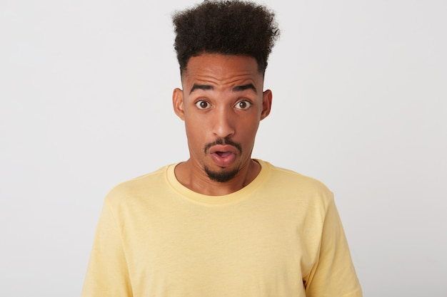 Portrait de hébété jeune attrayant curly dark skinned guy non rasé arrondissant avec étonnement ses yeux bruns