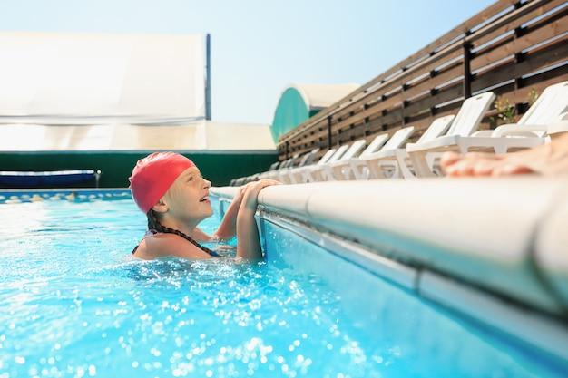 Le portrait de l'heureuse belle adolescente souriante à la piscine
