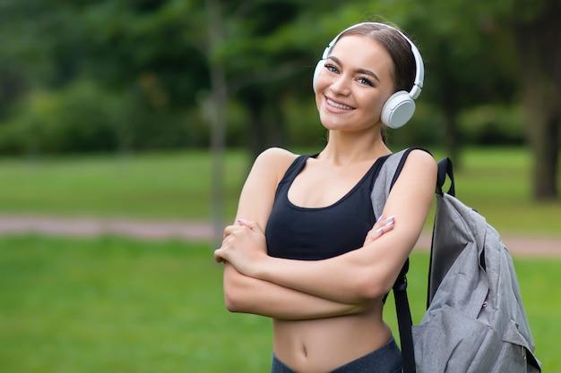Portrait de l'heureuse belle fille en forme positive, jeune femme sportive mince de remise en forme sans fil
