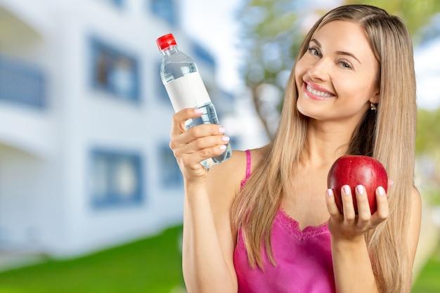 Portrait de heureuse belle jeune femme souriante mange une pomme rouge