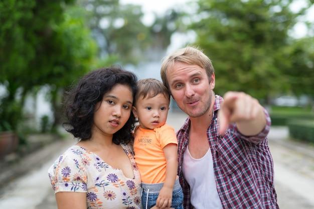 Portrait de l'heureuse famille multiethnique avec un enfant se liant ensemble à l'extérieur