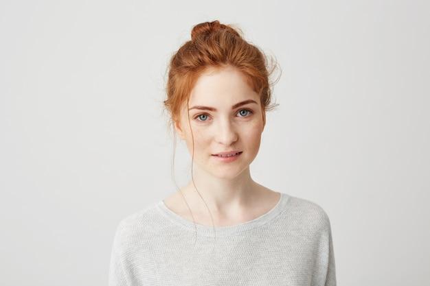 Portrait de heureuse fille tendre de gingembre aux yeux bleus et taches de rousseur souriant.