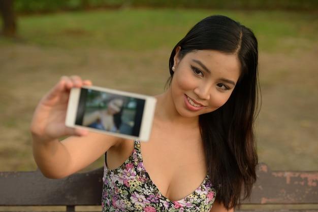 Portrait de l'heureuse jeune belle femme asiatique prenant selfie dans le parc