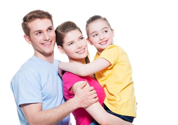Portrait de l'heureuse jeune famille avec enfant en chemises multicolores - isolé sur mur blanc.