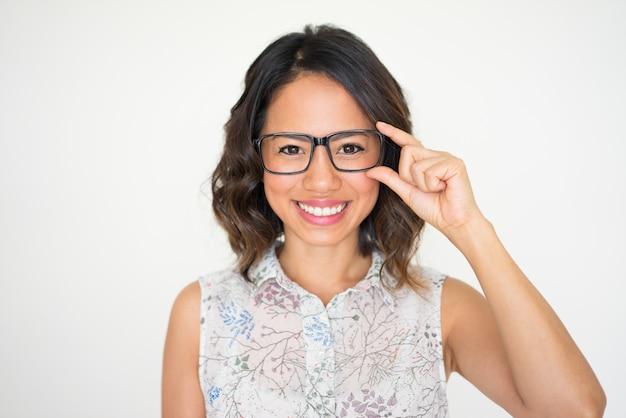 Portrait de l'heureuse jeune femme en ajustant les lunettes