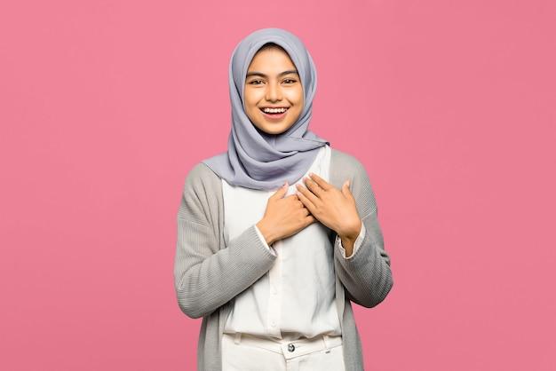 Portrait de l'heureuse jeune femme asiatique garde les mains sur la poitrine près du cœur