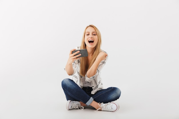 Portrait de l'heureuse jeune femme décontractée regardant téléphone mobile