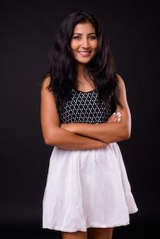 Portrait de l'heureuse jeune femme indienne belle souriante avec les bras croisés