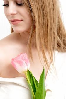 Un portrait d'une heureuse jeune femme de race blanche avec les yeux fermés et une tulipe rose sur un fond blanc avec copie espace