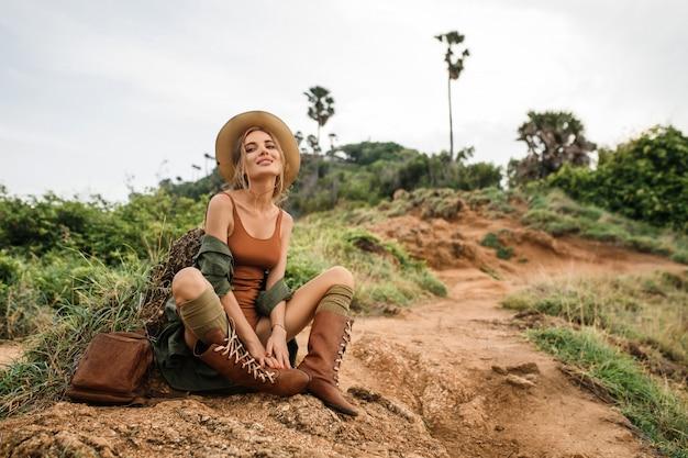 Portrait d'heureuse jeune femme avec sac à dos explorant la steppe sauvage. fille élégante hipster en vêtements de style chapeau et boho. concept de voyage et de voyage. moment d'ambiance incroyable