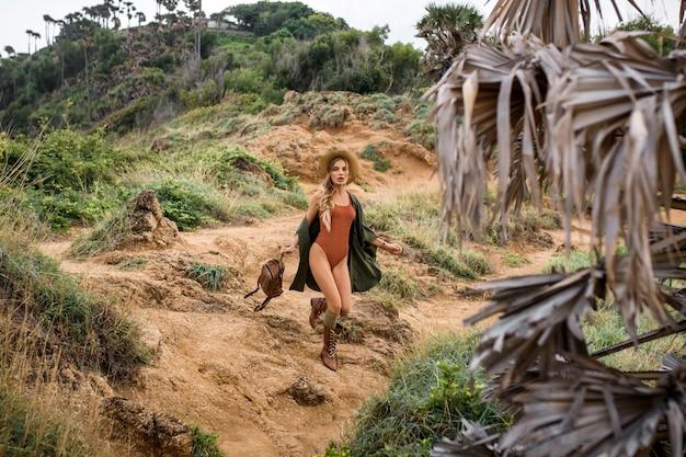 Portrait heureuse jeune femme avec sac à dos explorant les steppes sauvages. fille élégante hipster en vêtements de style chapeau et boho. voyage et envie de voyager. moment d'ambiance incroyable