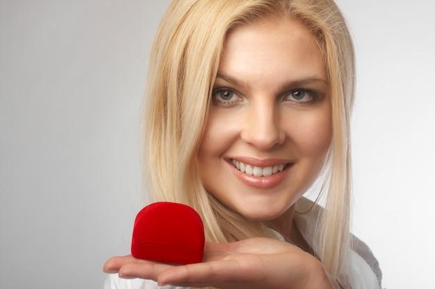Portrait d'heureuse jeune femme tenant un cadeau