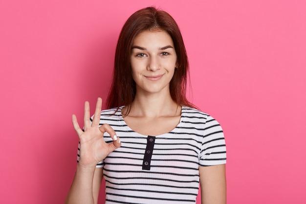 Portrait de l'heureuse jeune fille brune montrant le geste ok avec les doigts, avec un sourire charmant, a d'excellentes nouvelles, portant un t-shirt rayé.