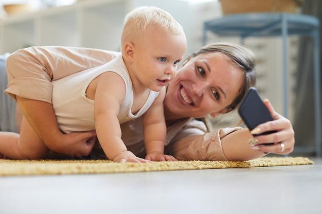 Portrait de l'heureuse jeune mère prenant selfie avec son bébé