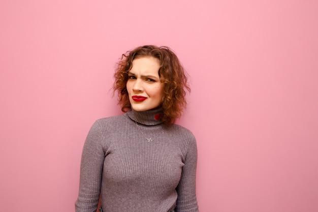Portrait de l'heureuse jolie dame en pull gris et cheveux bouclés