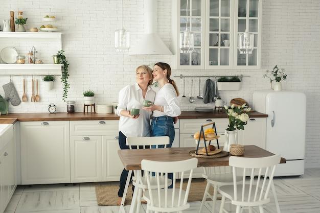 Portrait d'une heureuse mère et fille âgées dans la cuisine