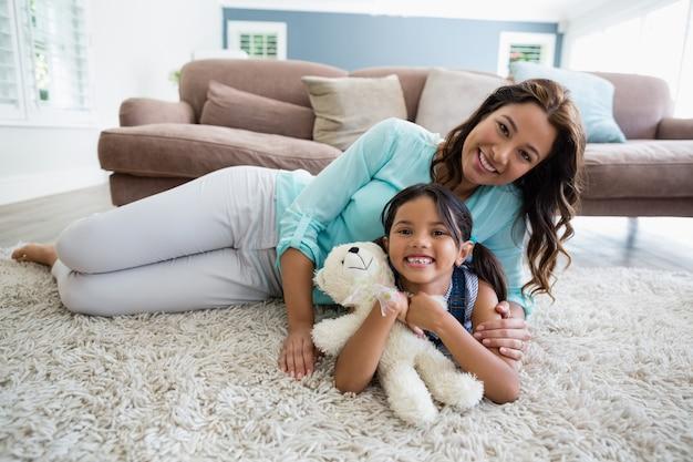 Portrait de l'heureuse mère et fille allongée sur un tapis