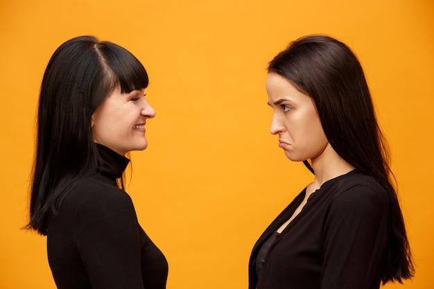 Un portrait d'une heureuse mère et fille au studio sur fond d'or. couleurs à la mode. concept d'émotions positives humaines et d'expressions faciales. vue de profil