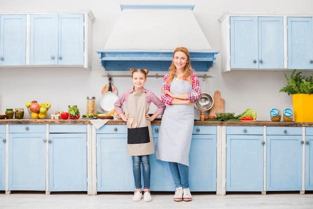 Portrait de l'heureuse mère et fille en tablier debout dans la cuisine