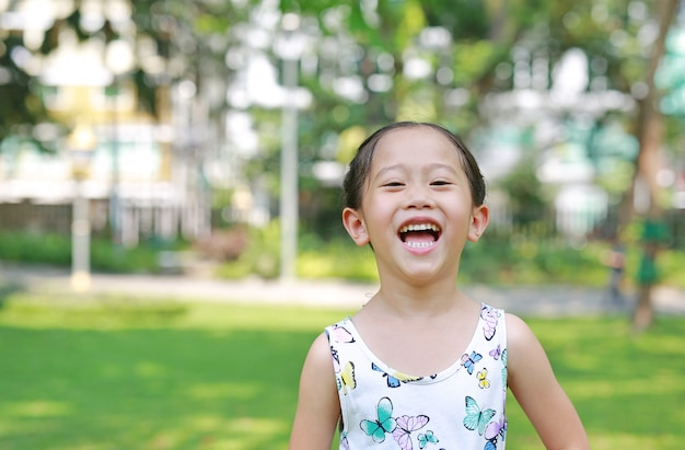 Portrait d'heureuse petite fille asiatique dans un parc verdoyant et ensoleillé.