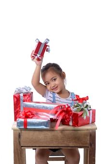 Portrait de heureuse petite fille asiatique avec de nombreux coffrets cadeaux isolé sur blanc