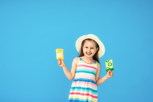 Portrait heureuse petite fille chapeau de paille avec crème glacée textile sur bleu