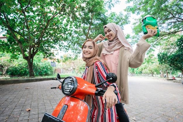 Portrait de l'heureux ami musulman équitation scooter moto ensemble en plein air
