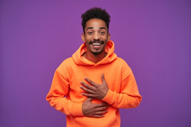 Portrait d'heureux beau jeune homme brune à la peau foncée bouclée avec barbe gardant les paumes sur sa poitrine tout en se réjouissant de bonnes nouvelles et souriant joyeusement, isolé sur violet