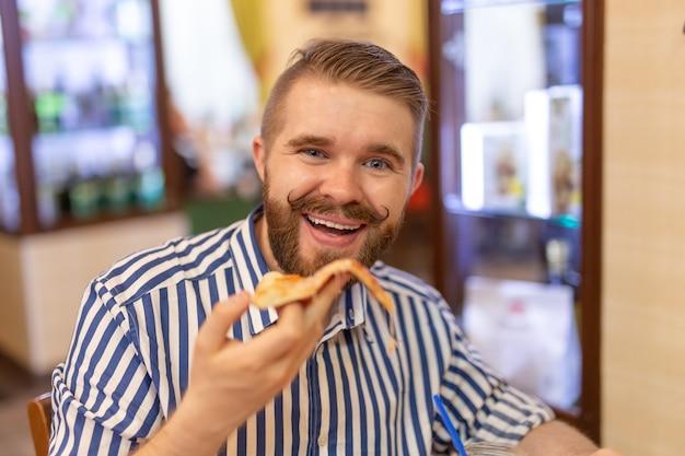 Portrait d'un heureux beau jeune homme avec une moustache et une barbe en train de manger un morceau de pizza dans un café. le concept de restauration rapide malsaine.
