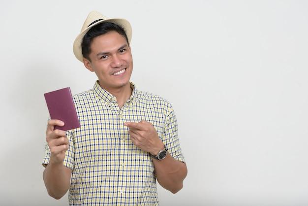 Portrait d'heureux beau touriste asiatique homme montrant un passeport