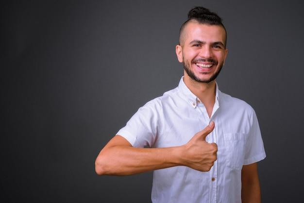 Portrait d'heureux bel homme turc barbu donnant les pouces vers le haut