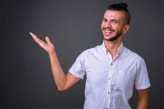 Portrait d'heureux bel homme turc barbu montrant quelque chose