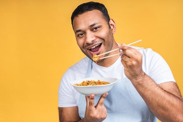 Portrait de l'heureux chef noir afro-américain indien cuisine des pâtes. cuisine, profession, haute cuisine, concept de nourriture et de personnes isolé sur fond jaune.