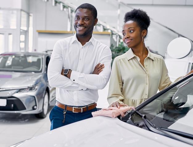 Portrait de l'heureux couple afro-américain de vérifier une voiture chez un concessionnaire moderne