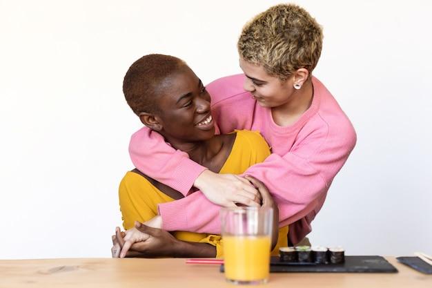 Portrait d'un heureux couple homosexuel multiethnique étreignant et souriant