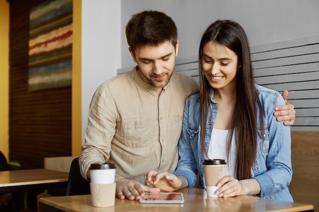 Portrait d'heureux couple de jeunes assis dans la cafétéria, boire du thé et chercher un appartement sur une tablette numérique. concept de mode de vie.