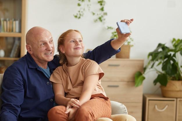 Portrait d'heureux grand-père prenant selfie via smartphone avec jolie petite fille dans un intérieur confortable