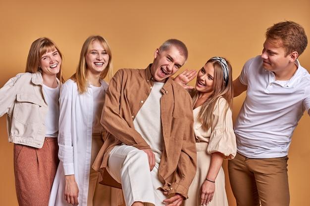 Portrait de l'heureux groupe de jeunes caucasiens s'amusant