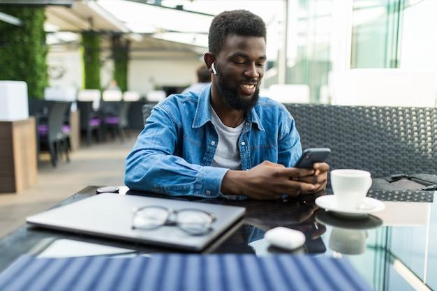 Portrait d'heureux homme d'affaires africain à l'aide de téléphone tout en travaillant sur un ordinateur portable dans un restaurant